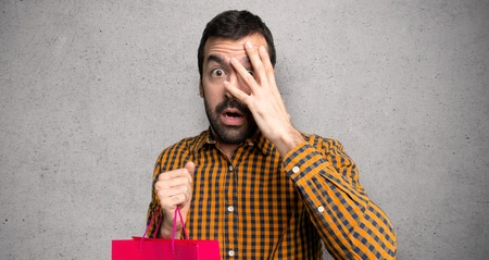 Man with shopping bags with surprise and shocked facial expression over textured wall