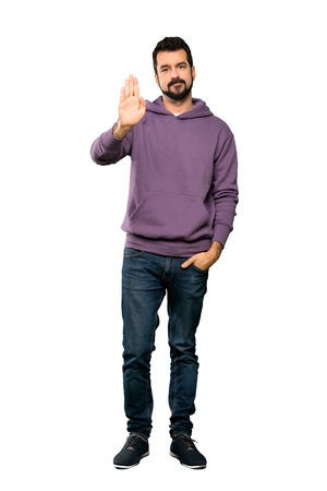 Full-length shot of Handsome man with sweatshirt making stop gesture over isolated white background Imagens