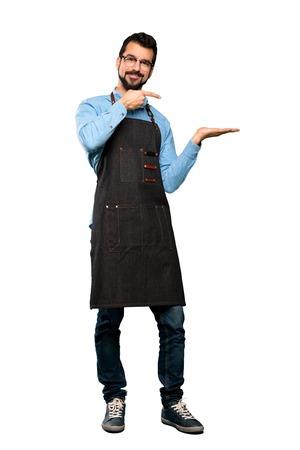 Ganzkörperaufnahme eines Mannes mit Schürze, der ein imaginäres Exemplar auf der Handfläche hält, um eine Anzeige über isoliertem weißem Hintergrund einzufügen