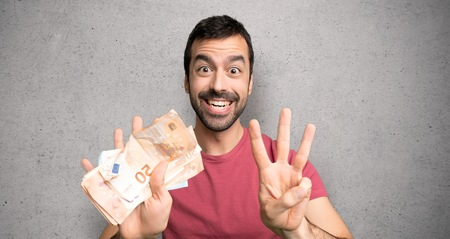 Man taking a lot of money counting eight with fingers over textured wall