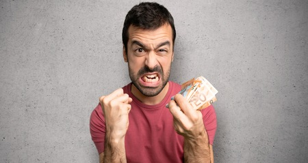 Man taking a lot of money frustrated by a bad situation over textured wall