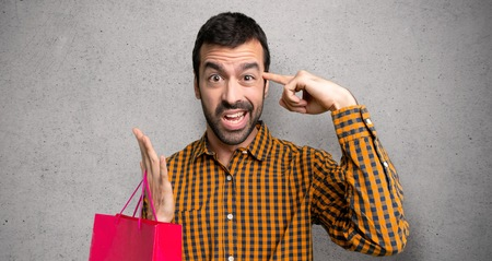 Man with shopping bags making the gesture of madness putting finger on the head over textured wall