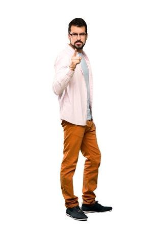 Disparo de cuerpo entero de un hombre guapo con barba frustrado y apuntando hacia el frente sobre fondo blanco aislado Foto de archivo