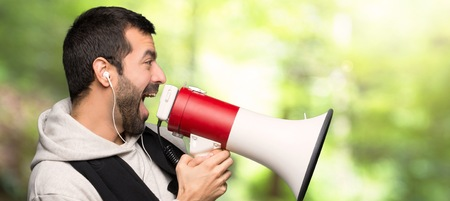 Sport man shouting through a megaphone to announce something in lateral position in a park Imagens