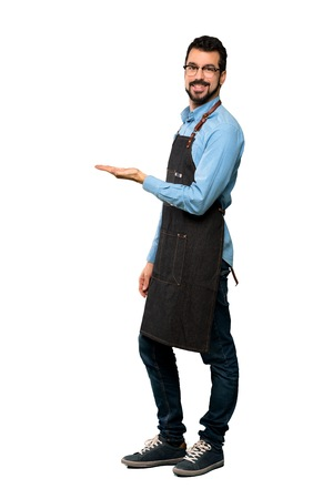 Full-length shot of Man with apron presenting an idea while looking smiling towards over isolated white background