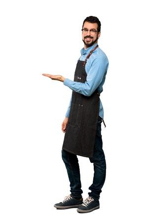 Ganzaufnahme eines Mannes mit Schürze, der eine Idee präsentiert, während er lächelnd auf einen isolierten weißen Hintergrund blickt
