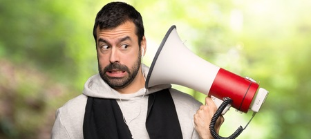Sport man taking a megaphone that makes a lot of noise in a park Stock Photo