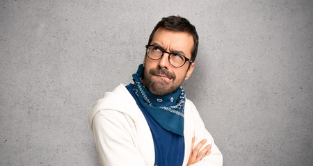 Handsome man with glasses with confuse face expression while bites lip over textured wall