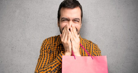Man with shopping bags smiling a lot while covering mouth over textured wall