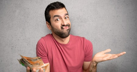 Man taking a lot of money unhappy and frustrated with something because not understand something over textured wall
