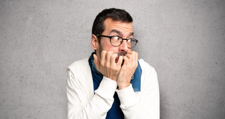 Handsome man with glasses is a little bit nervous and scared putting hands to mouth over textured wall