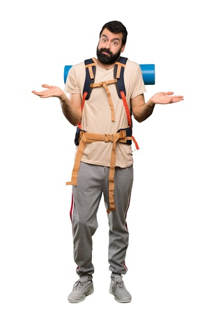 Hiker man having doubts while raising hands over isolated white background