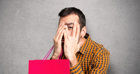 Man with shopping bags covering eyes by hands and looking through the fingers over textured wall