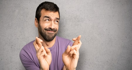 Handsome man with fingers crossing and wishing the best over textured wall