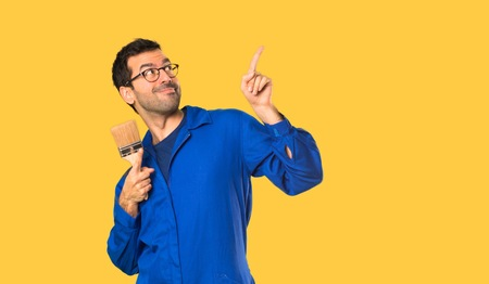 Painter man pointing with the index finger and looking up on isolated yellow background