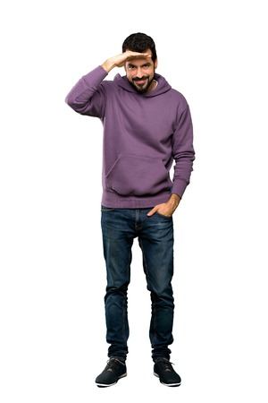 Full-length shot of Handsome man with sweatshirt looking far away with hand to look something over isolated white background Stock Photo