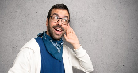 Handsome man with glasses listening to something by putting hand on the ear over textured wall