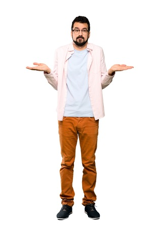 Full-length shot of Handsome man with beard having doubts while raising hands over isolated white background Stock Photo