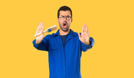 Painter man making stop gesture for disappointed with an opinion on isolated yellow background