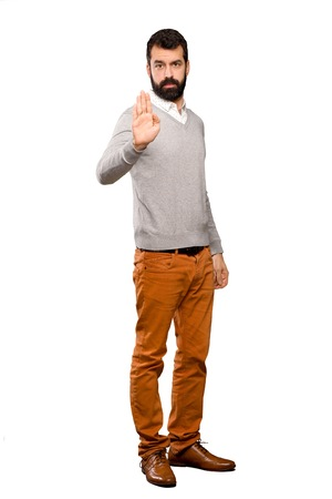 Handsome man making stop gesture over isolated white background