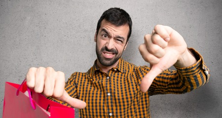 Man with shopping bags showing thumb down with both hands over textured wall Stock Photo