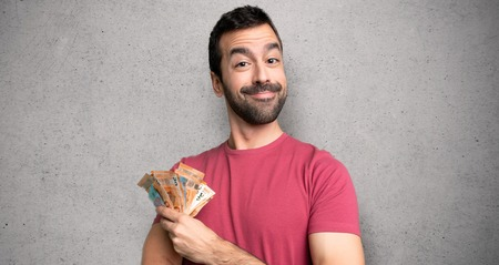 Man taking a lot of money keeping the arms crossed in frontal position over textured wall