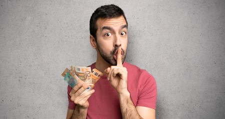 Man taking a lot of money showing a sign of silence gesture putting finger in mouth over textured wall Stock Photo