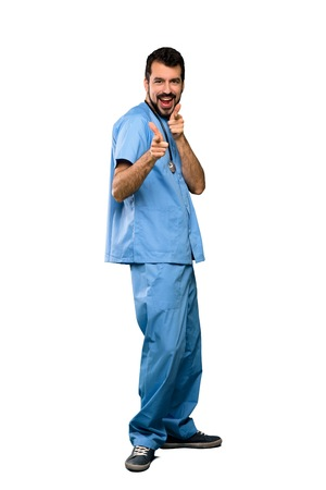 Full-length shot of Surgeon doctor man pointing to the front and smiling over isolated white background