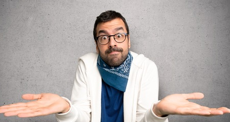Handsome man with glasses having doubts while raising hands and shoulders over textured wall
