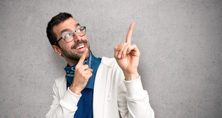 Handsome man with glasses pointing with the index finger and looking up over textured wall