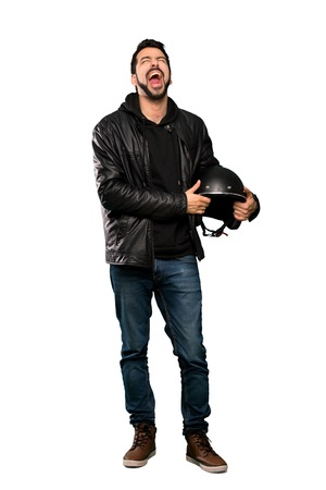 Full-length shot of Biker man shouting to the front with mouth wide open over isolated white background