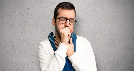 Handsome man with glasses is suffering with cough and feeling bad over textured wall Banque d'images
