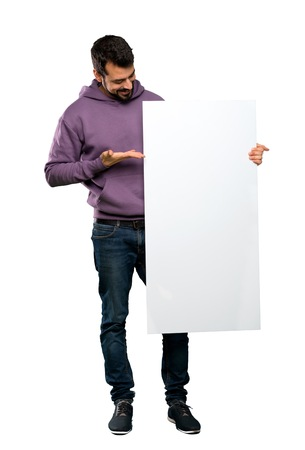 Full-length shot of Handsome man with sweatshirt holding an empty placard over isolated white background