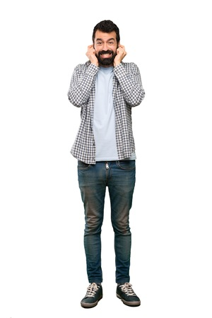 Handsome man with beard frustrated and covering ears over isolated white background