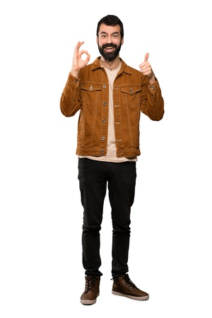 Handsome man with beard showing ok sign and thumb up gesture over isolated white background