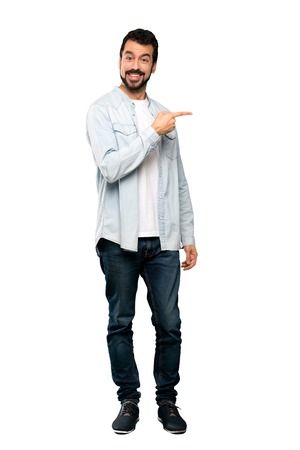 Full-length shot of Handsome man with beard pointing finger to the side over isolated white background