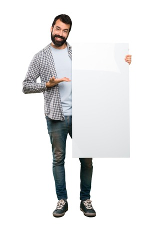 Happy Handsome man with beard holding an empty placard over isolated white background Stock Photo