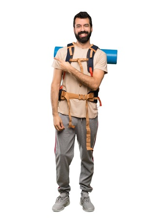 Hiker man pointing to the side to present a product over isolated white background