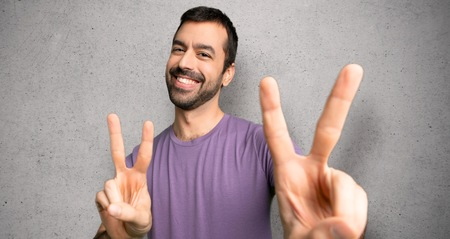 Handsome man smiling and showing victory sign with both hands over textured wall