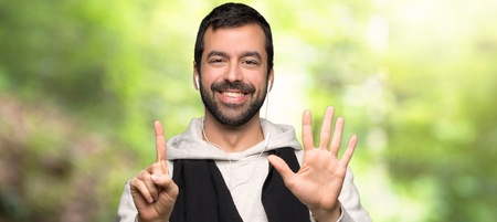 Sport man counting six with fingers in a park