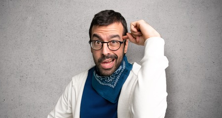 Handsome man with glasses making the gesture of madness putting finger on the head over textured wall