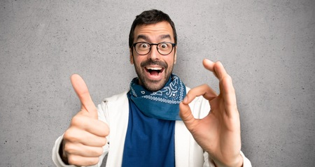 Handsome man with glasses showing ok sign with and giving a thumb up gesture over textured wall