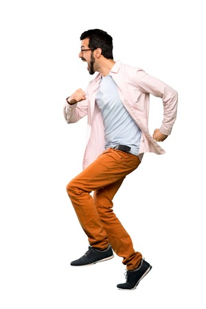 Full-length shot of Handsome man with beard running fast over isolated white background Stock Photo