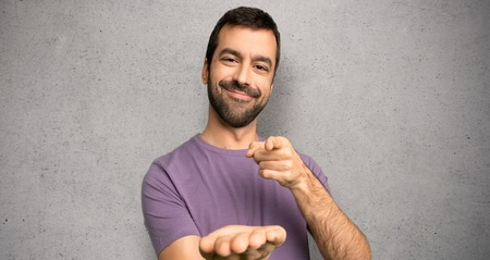 Handsome man holding copyspace imaginary on the palm to insert an ad over textured wall