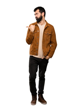 Handsome man with beard unhappy and pointing to the side over isolated white background Stock Photo