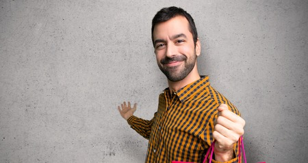Man with shopping bags pointing back and presenting a product over textured wall Stock Photo