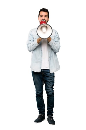 Full-length shot of Handsome man with beard shouting through a megaphone over isolated white background Stock Photo
