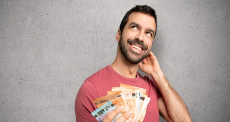 Man taking a lot of money thinking an idea while scratching head over textured wall