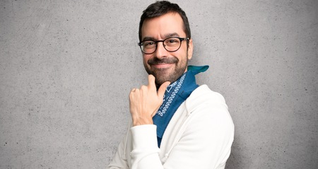Handsome man with glasses smiling with a sweet expression over textured wall Stock Photo
