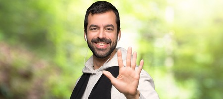 Sport man counting five with fingers in a park Stock Photo